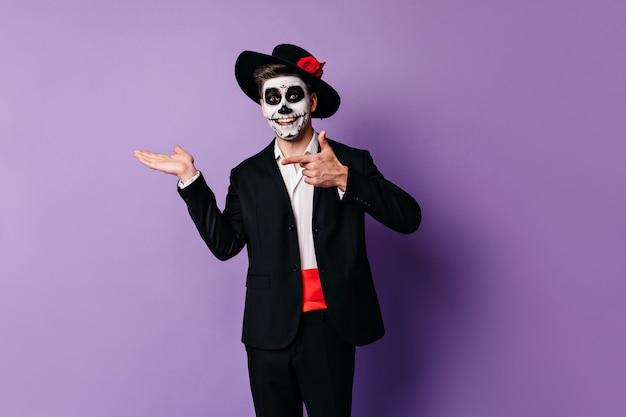 Vrolijke, enthousiaste man met geverfd gezicht voor halloween wijst met zijn vinger naar de plaats voor tekst op paarse achtergrond.