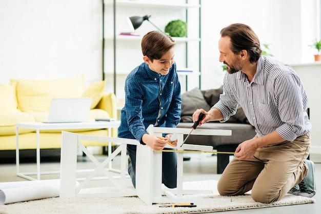 Vrolijke enthousiaste man zittend op de vloer met zijn positieve zoon en wijst met een schroevendraaier naar het stoelgedeelte