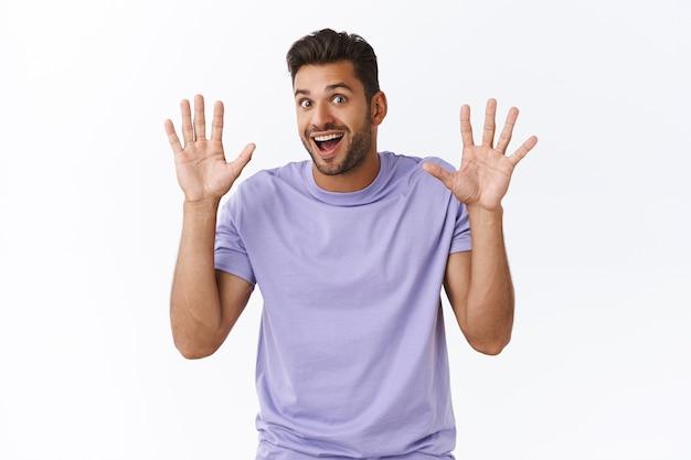 Vrolijke enthousiaste moderne man in paars t-shirt heeft niets te verbergen, handen opsteken in overgave of herbehandeling, vreugdevol glimlachen, handen zwaaien, vriendelijk begroetingsgebaar, witte muur