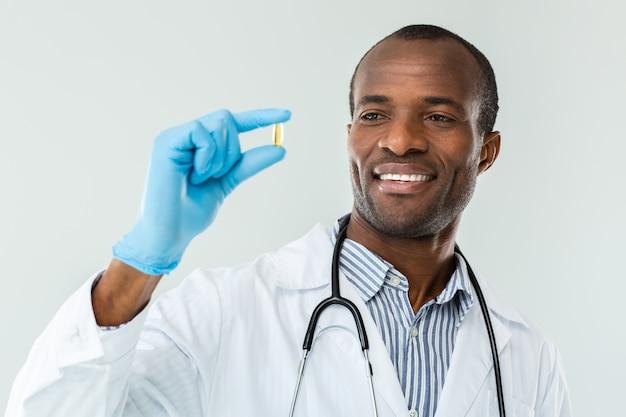 Vrolijke ervaren arts die lacht terwijl hij een pil vasthoudt