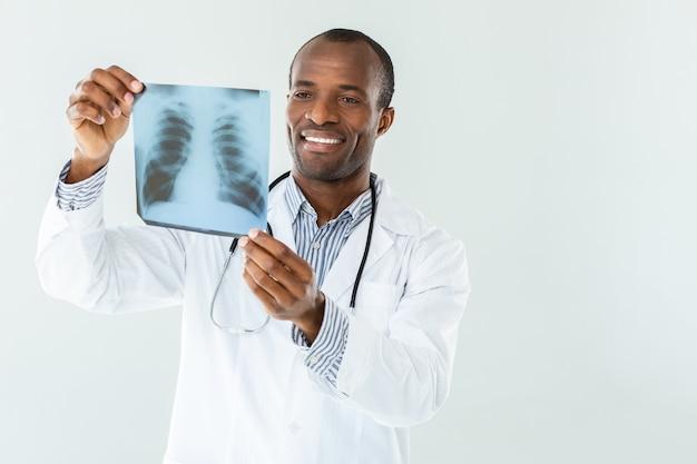 Vrolijke ervaren arts die röntgenscan houdt terwijl hij tegen een witte muur staat