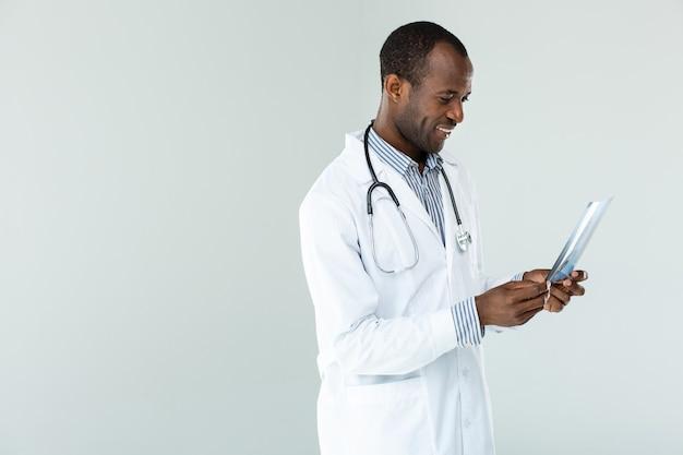 Vrolijke ervaren professionele arts die zich tegen witte muur bevindt
