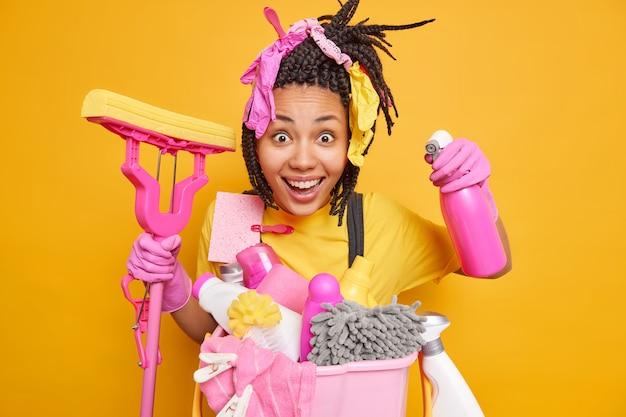 Vrolijke etnische huisvrouw heeft gevlochten poses met dweil en wasmiddelfles die graag schoonmaakt