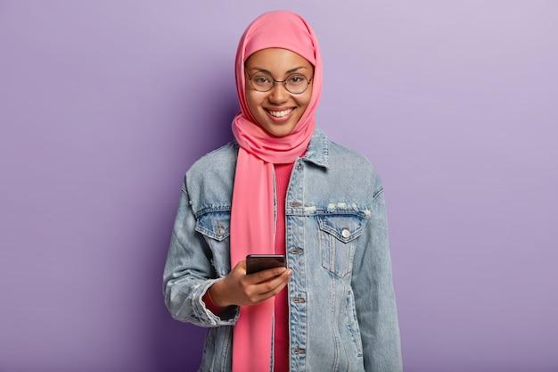 Vrolijke etnische vrouw met zachte glimlach, scrollt nieuwsfeed op internet op mobiele telefoon, leest interessant uitnodigingsbericht, gekleed in roze hija en ronde bril, geïsoleerd over paarse muur