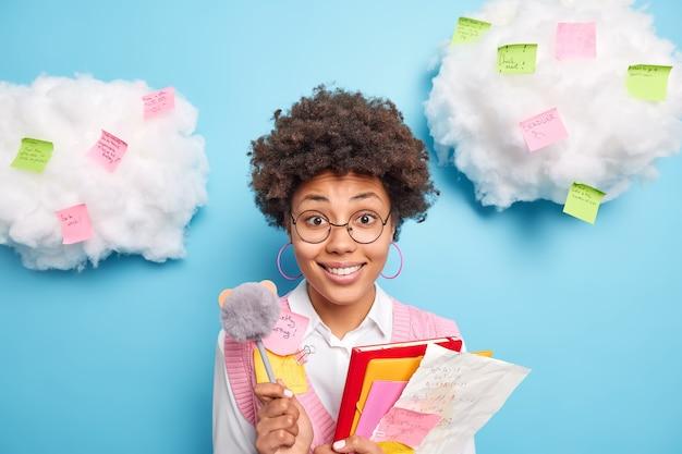 Vrolijke etnische vrouwelijke student houdt papieren mappen en pen gaat unveristy op lezingen draagt ronde bril formele kleding omringd door kleurrijke stickers geïsoleerd over blauwe muur