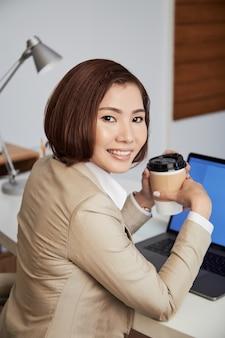 Vrolijke etnische zakenvrouw met koffie