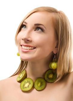 Vrolijke europese blonde vrouw met kort haar poseren met groene rijpe druif in handen