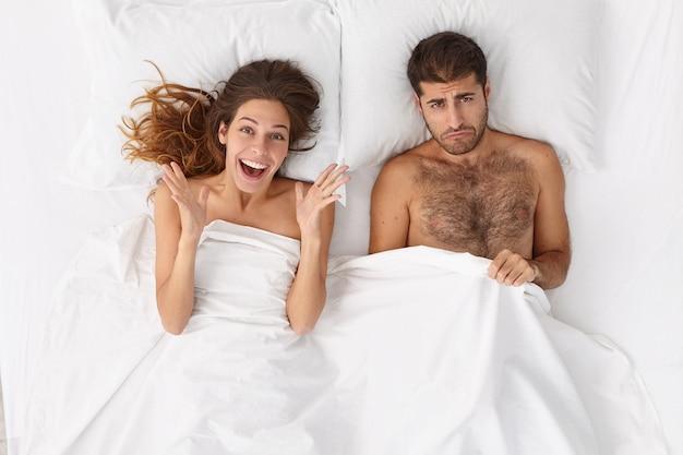 Vrolijke europese vrouw kijkt graag, ontevreden echtgenoot poseert in de buurt van in bed in de slaapkamer, heeft problemen met de gezondheid, erectiestoornissen. probleem van familiepaar met seksueel leven.