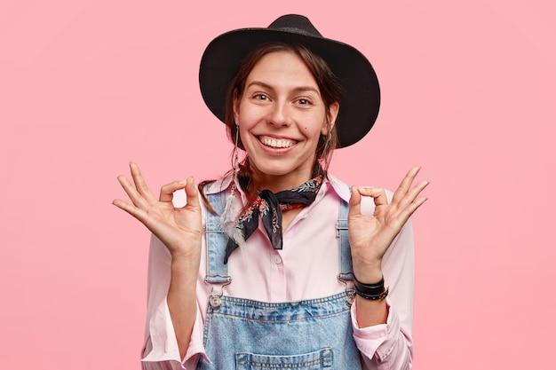 Vrolijke europese vrouw met een positieve glimlach, maakt goed gebaar met beide handen, toont haar instemming en verheugt zich over haar succes, poseert tegen roze muur