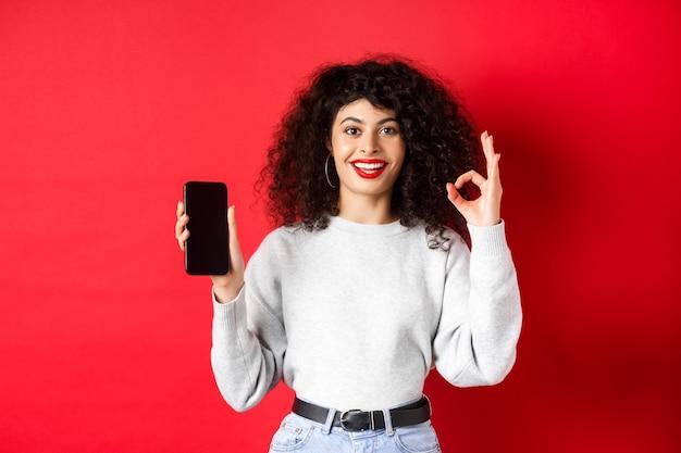 Vrolijke europese vrouw met krullend haar, leeg scherm van mobiele telefoon en goed gebaar, tevreden glimlachen, goede app of promotie prijzen, rode achtergrond