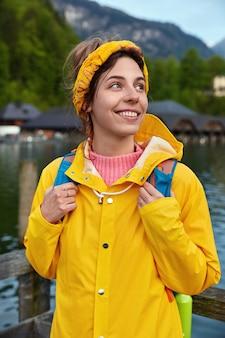 Vrolijke europese vrouwelijke toerist reist in de bergen, vormt in de buurt van meer, geniet van zonnige warme dag