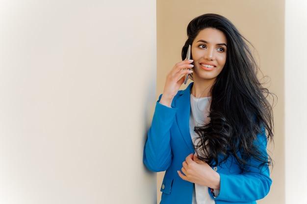 Vrolijke europese zakenvrouw praat over haar prestaties, geniet van goed nieuws op het werk