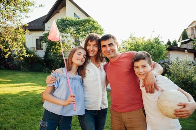Vrolijke familie die picknick heeft die zich op groene aard in park verenigt