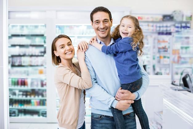 Vrolijke familie die samenkwam en in de apotheek stond en naar de camera lachte