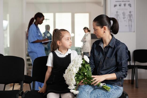 Vrolijke familie die tijdens medisch onderzoek in de gang van het ziekenhuis wacht