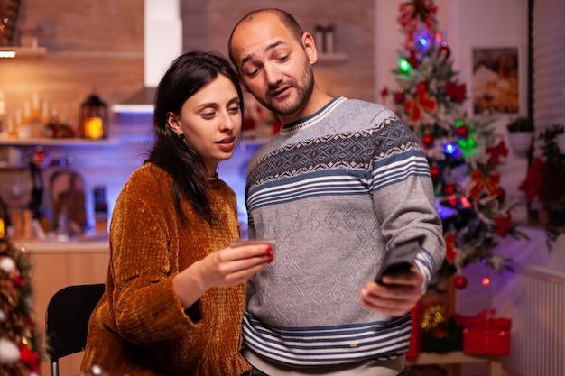 Vrolijke familie doet online winkelen kerstcadeau met creditcard voor betaling