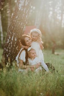 Vrolijke familie in een park, moeder en hun twee mooie dochter om op het gras te zitten terwijl zij camera bekijken.