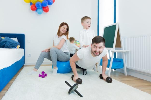 Vrolijke familie, jonge man vader en jonge vrouw moeder, doen ochtendgymnastiek met hun twee jonge zonen. breng samen tijd door in de kinderkamer