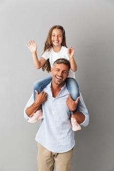 Vrolijke familie lachend terwijl meisje met plezier en zittend op de nek van haar gelukkige vader, geïsoleerd over grijs