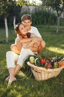 Vrolijke familie met biologische groenten in de tuin. gemengde biologische groente in rieten mand. moeder met zoon in een achtertuin.