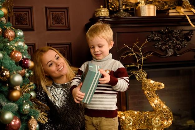 Vrolijke familie met kerstcadeaus door de boom.
