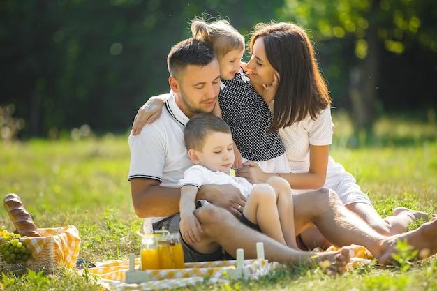 Vrolijke familie met picknick. ouders eten buiten met hun kinderen.