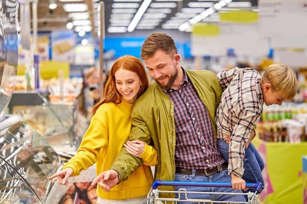 Vrolijke familie met rusteloze grappige zoon in supermarkt, man en vrouw kiezen van voedsel in de winkel, mannelijke gekke jongen in handen houden