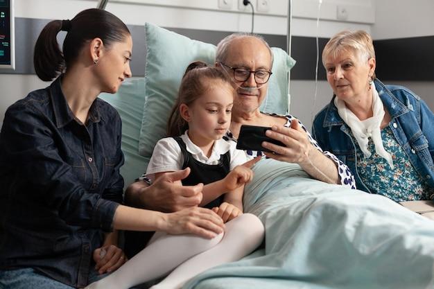 Vrolijke familie op bezoek bij bejaarde grootvader in ziekenhuisafdeling tijdens klinisch herstel