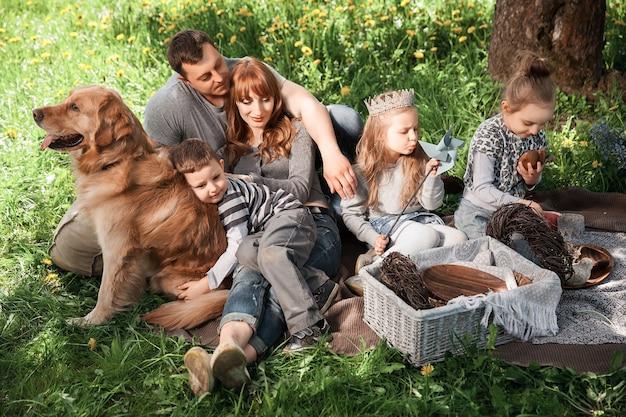 Vrolijke familie op een picknick met een hond die op het gras ligt