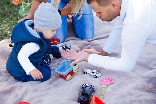 Vrolijke familie op een picknick op een lentedag. de vader toont de zoon van een kever in de hand.