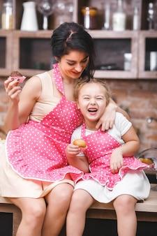 Vrolijke familie plezier in de keuken. jonge moeder en haar dochtertje bakken samen