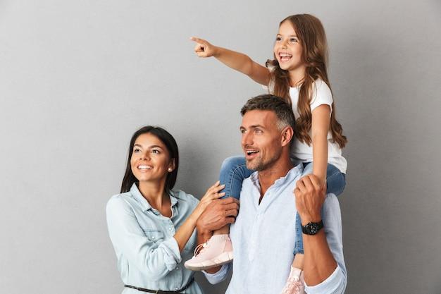 Vrolijke familie vrouw en man glimlachend en opzij kijken terwijl mooi meisje zittend op de nek van haar gelukkige vader, geïsoleerd over grijs