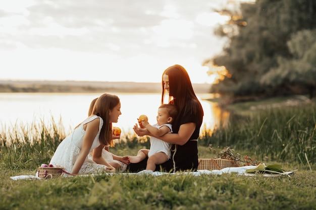 Vrolijke familie zittend op het groene gras tijdens een zomerpicknick in de buurt van het meer