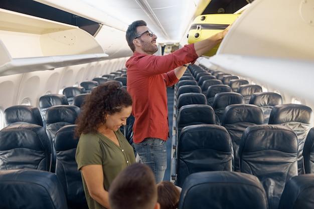 Vrolijke familieman die bagage in het compartiment zet terwijl hij samen met zijn vrouw en dochtertje per vliegtuig reist. familievakantie, vervoersconcept