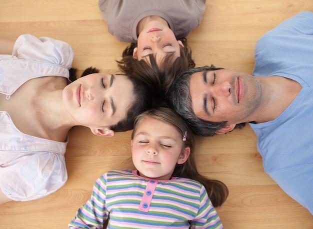 Vrolijke familieslaap die op de vloer liggen