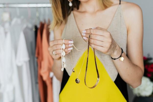 Vrolijke fashionista die sieraden selecteert in een winkel