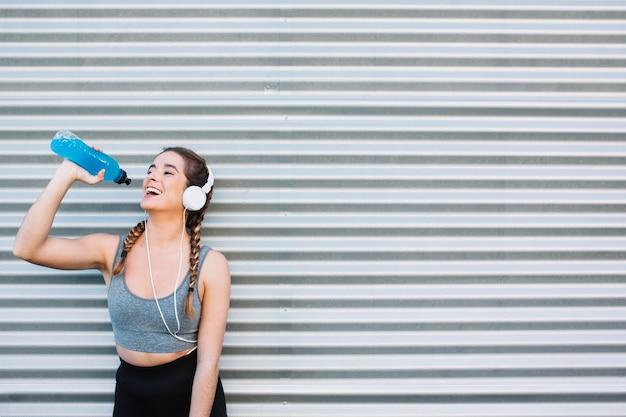 Vrolijke fit vrouw in koptelefoon drinken