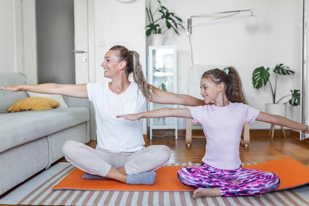 Vrolijke fitte vrouw en dochtertje doen lunges-oefeningen terwijl ze samen trainen voor een laptop in een modern appartement. familie moeder en kind dochter zijn bezig met fitness
