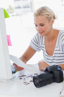 Vrolijke fotoredacteur die een contactblad bekijkt