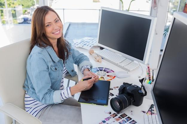 Vrolijke fotoredacteur die met een grafische tablet werkt