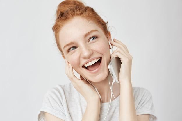 Vrolijke foxyvrouw die het luisteren muziek in hoofdtelefoons het glimlachen verheugen.