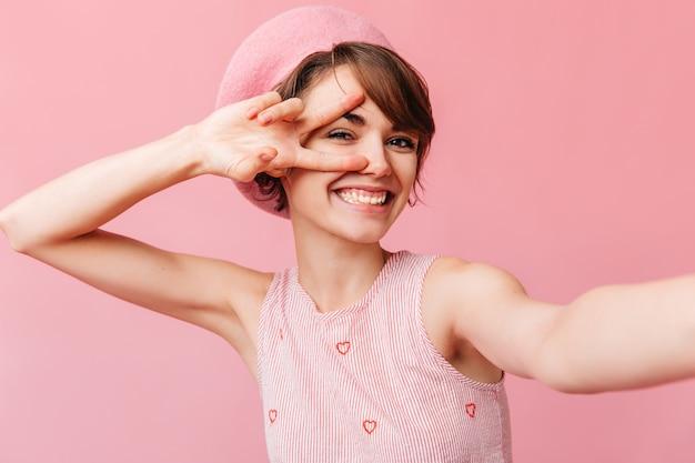Vrolijke franse vrouw die vredesteken toont
