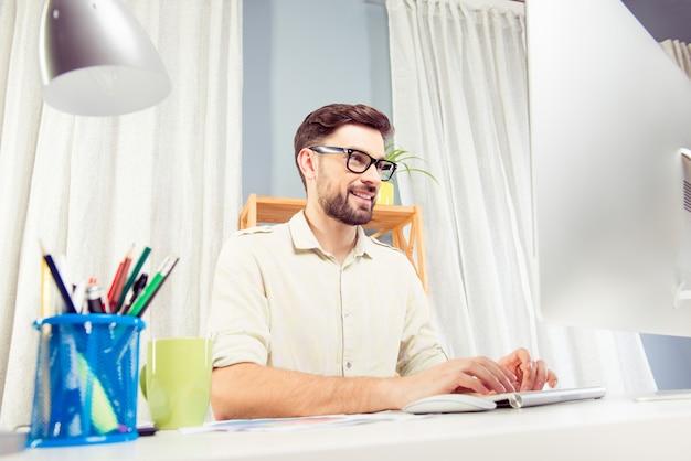 Vrolijke freelancer in glazen werken met pc en typen op kantoor