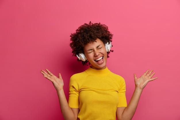 Vrolijke, geamuseerde, donkere, gekrulde jonge vrouw geniet van geweldige koptelefoonkwaliteit, prachtig geluid, handpalmen omhoog, luistert naar muziek, voelt zich tevreden met een goed lied, gekleed in gele kleren, heeft plezier