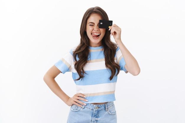 Vrolijke, geamuseerde, mooie moderne vrouw geeft de voorkeur aan creditcards, glimlacht vrolijk, opent een nieuwe bankrekening, tevreden grote cashback