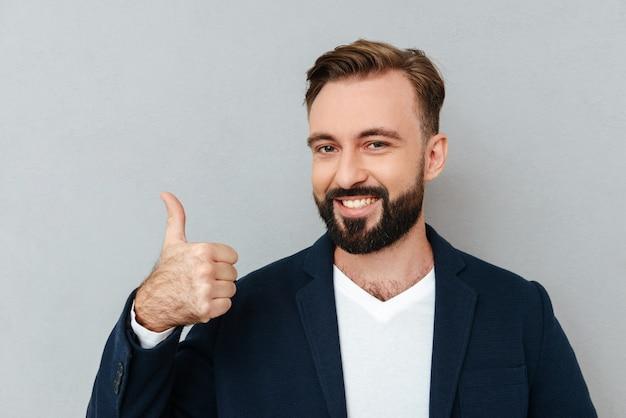 Vrolijke gebaarde mens in bedrijfskleren die duim tonen en de camera over grijs bekijken