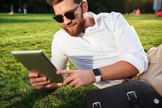 Vrolijke gebaarde mens in zonnebril die op gras in openlucht liggen en zijn tabletcomputer met behulp van