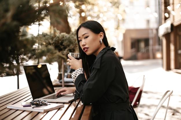 Vrolijke gebruinde aziatische vrouw in zwarte trenchcoat drinkt thee, werkt met laptop en zit buiten aan een houten bureau desk