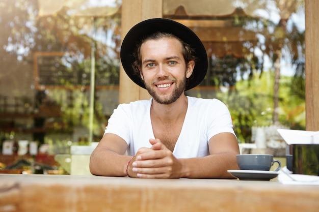 Vrolijke gebruinde student met dikke baard met goede koffie tijdens de lunch, gelukkig lachend, genietend van zomervakanties in tropisch land