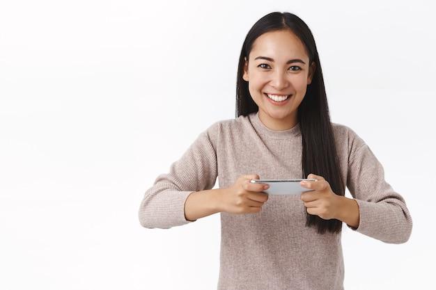 Vrolijke, gedurfde en enthousiaste knappe aziatische meid met donker haar, wil winnen in het spel, concurreren met vriend internet verbinden om arcade of race te spelen, smartphone horizontaal houden, glimlachend vermaakt